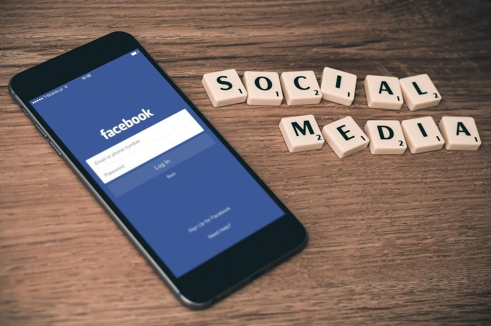 Smartphone sobre uma mesa com Facebook aberto e letras ao lado formando 'Social Media'