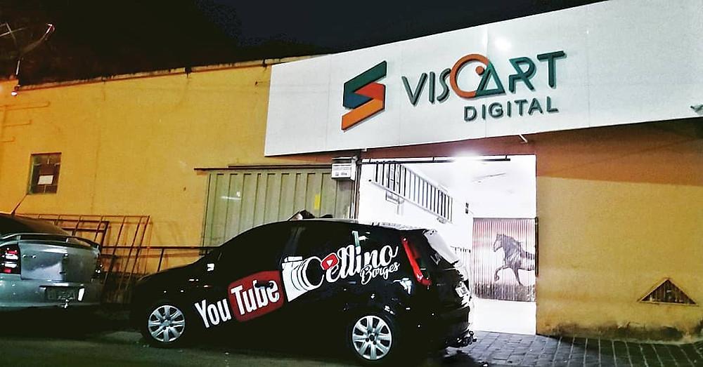 Carro do Celino personalizado com adesivos do seu canal em frente a uma oficina