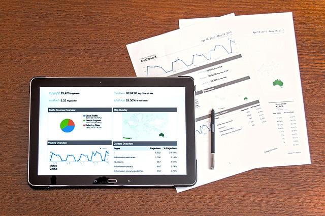 Tablet mostrando vários gráficos sobre papéis com gráficos também