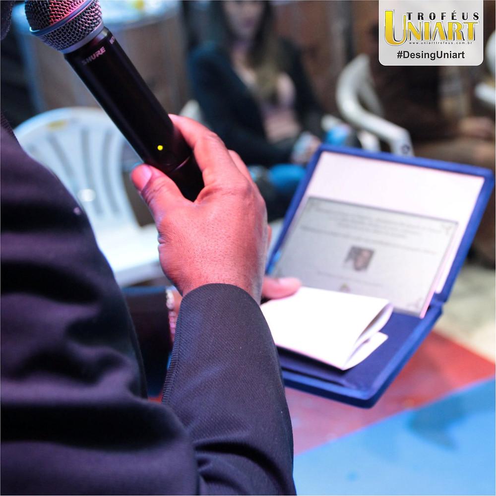 Pessoa falando ao microfone segurando placa de homenagem com estojo