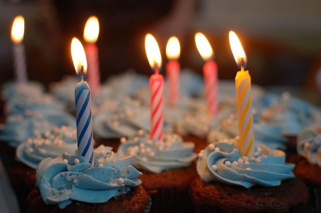 Vários cupcakes com velas coloridas e acesas em cima