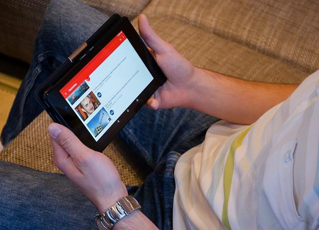 Homem sentado acessando YouTube pelo tablet