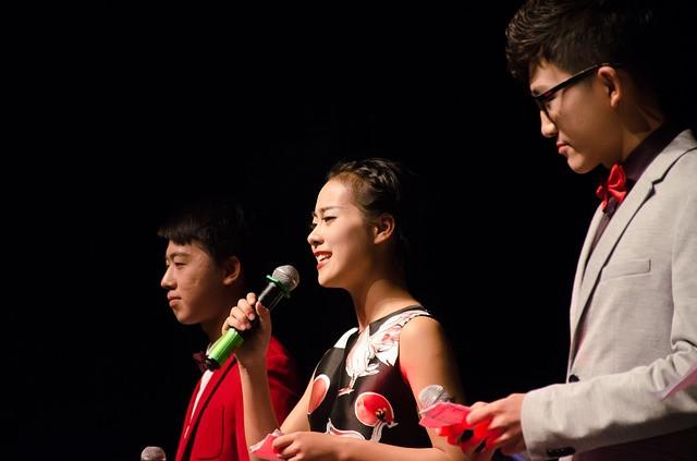 Mulher discursando em palco com dois homens ao seu lado