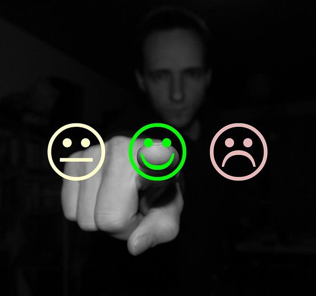 Homem apontando para emoji rosto feliz mostrando satisfação