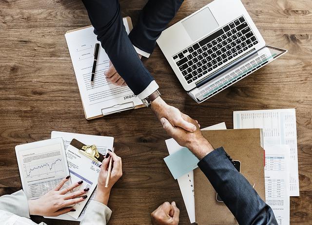 Mão fechando acordo sobre mesa com notebook e papéis