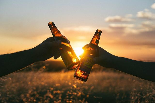 Duas pessoas brindando com cervejas ao pôr-do-sol ao fundo