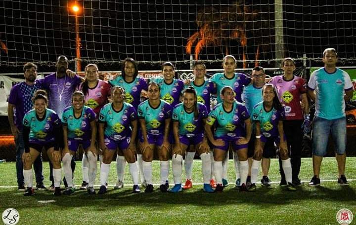 Equipe feminina de futebol com uniforme roxo e verde água