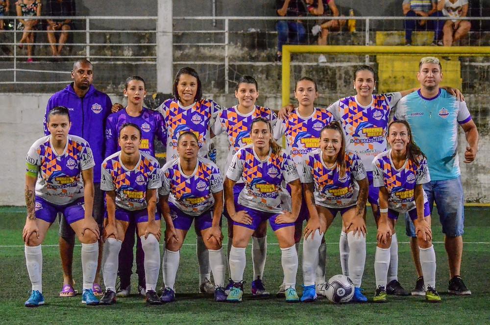 Equipe de futebol feminino com uniforme roxo e branco