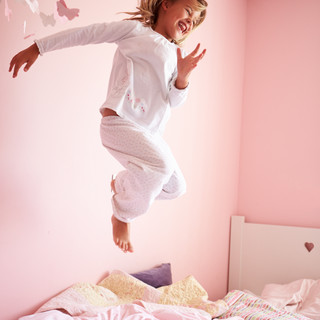 young-girl-jumping-on-her-bed-PNY3LAJ.jp