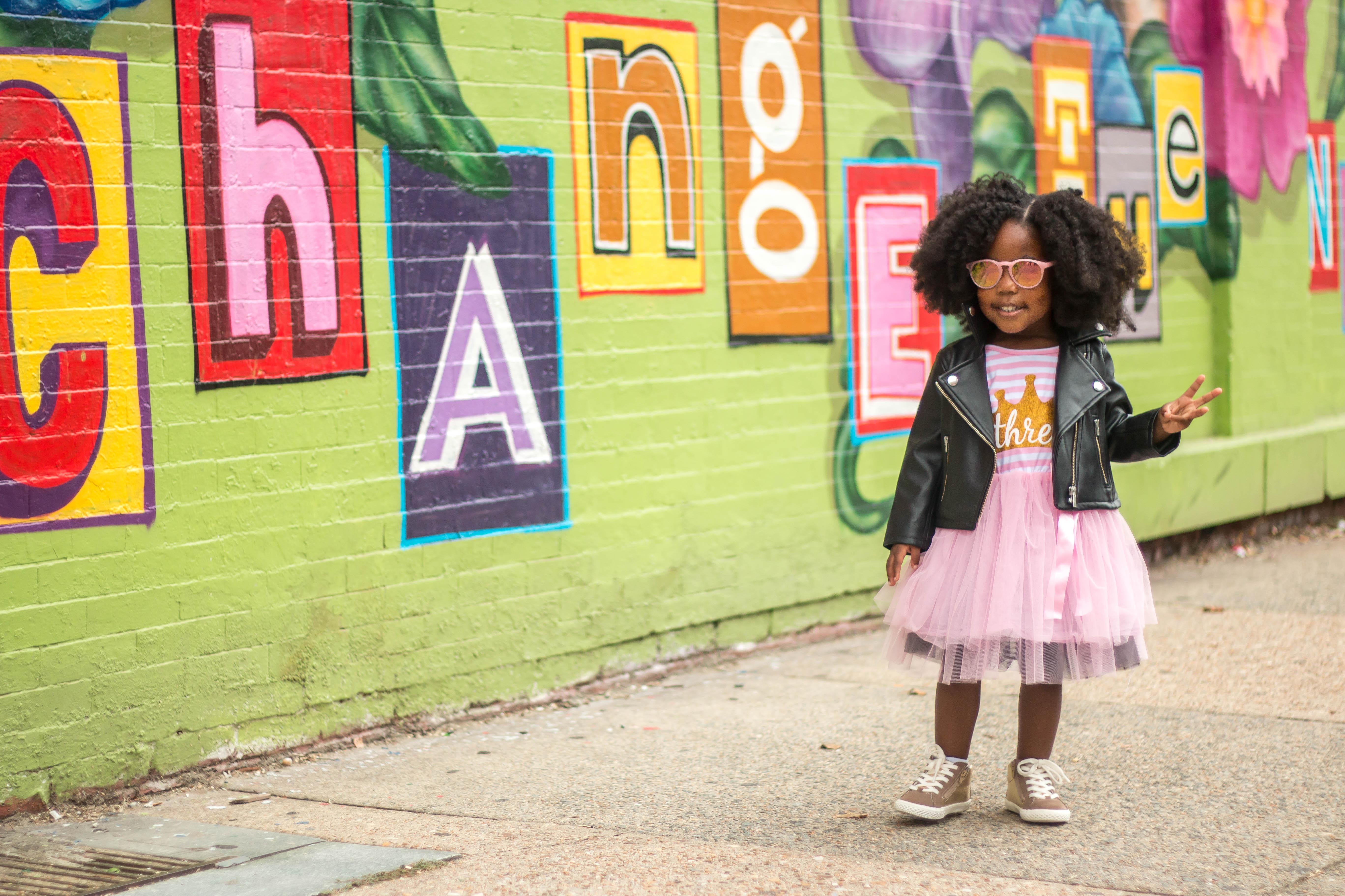 Little Girl Posing In Front of Mural