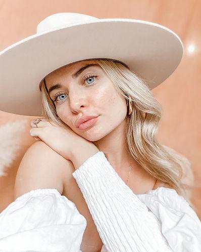 blonde woman wearing white hat close up shot