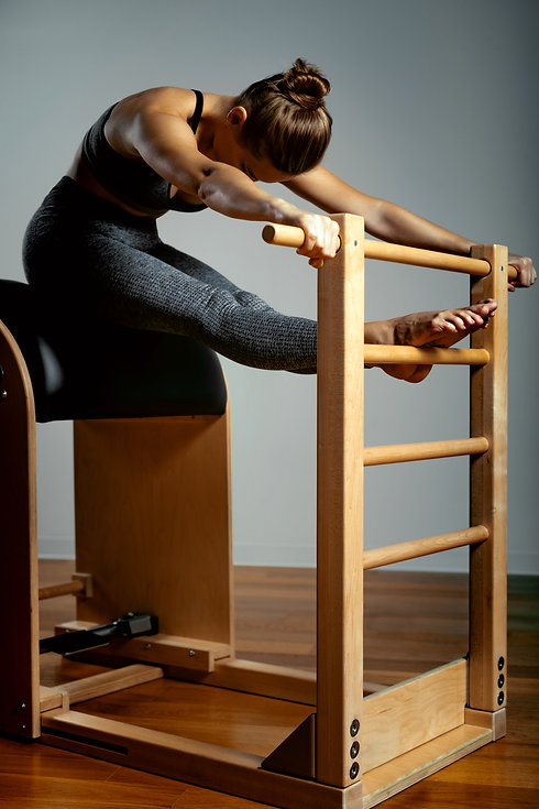 Pilates, fitness, sport, training and people concept - woman doing exercises on a small ba