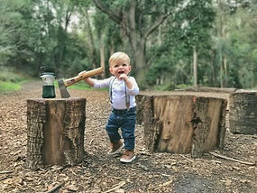 A toddler in a forest next to wood rounds and an axe. We are family people - this kiddo here is fourth generation in the family business!