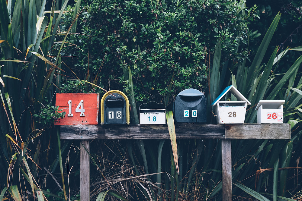 Row of 5 differently shaped mailboxes with the numbers 14, 16, 18, 20 and 28 on them. All perched on a wooden log with a backdrop of bushes.