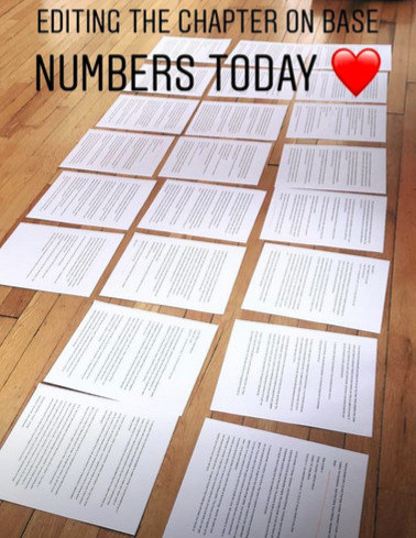 Pages from a book manuscript layed out on the floor and the words 'editing the chapter on base numbers today' written across.'