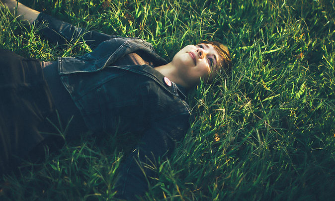 Novalee Wilder laying on her back on the grass staring at the sky.