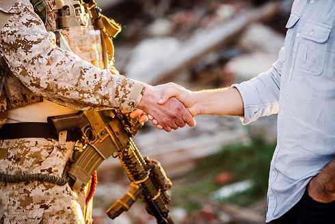 Soldier and civilian shaking hands on outdoor background.jpg
