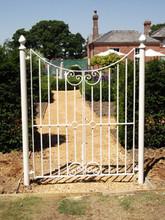 Bespoke double garden gate with wrought iron scrolls.