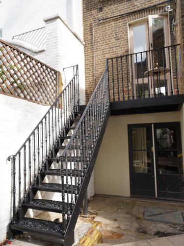Cast iron staircase and balcony with cast iron balusters finished in black – London.