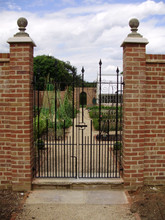 Bespoke double walled garden gate with cast iron finials.