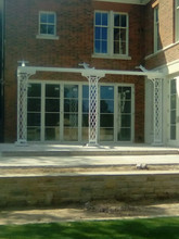 A traditional cast iron pergola finished in white.