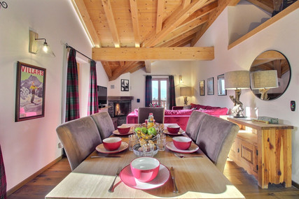 Living and dining room with open fireplace and access onto South and East balconies