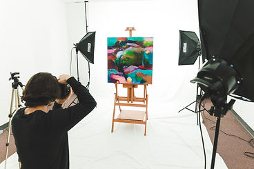 man taking photo of painting