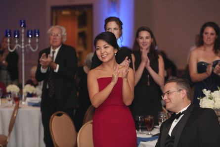 woman clapping in red dress at gala