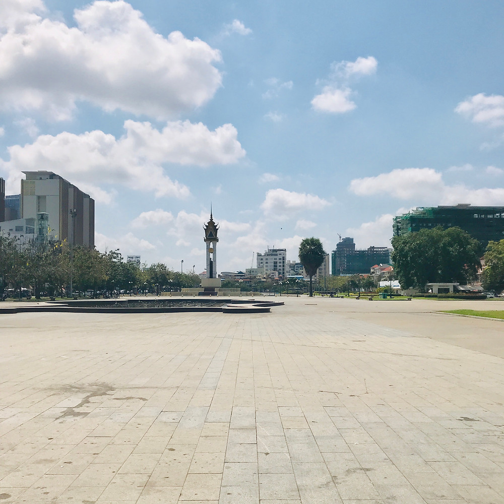 Empty square with trees and buildings in the background. Blue skies with clouds.