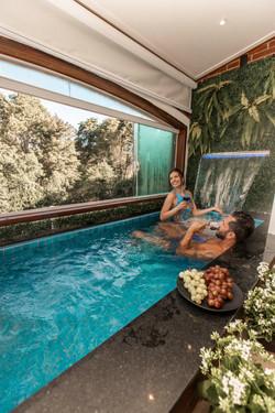 Chalé Panorâmico - Adorai Chalés - Casal conversando na piscina com cascata e contemplando
