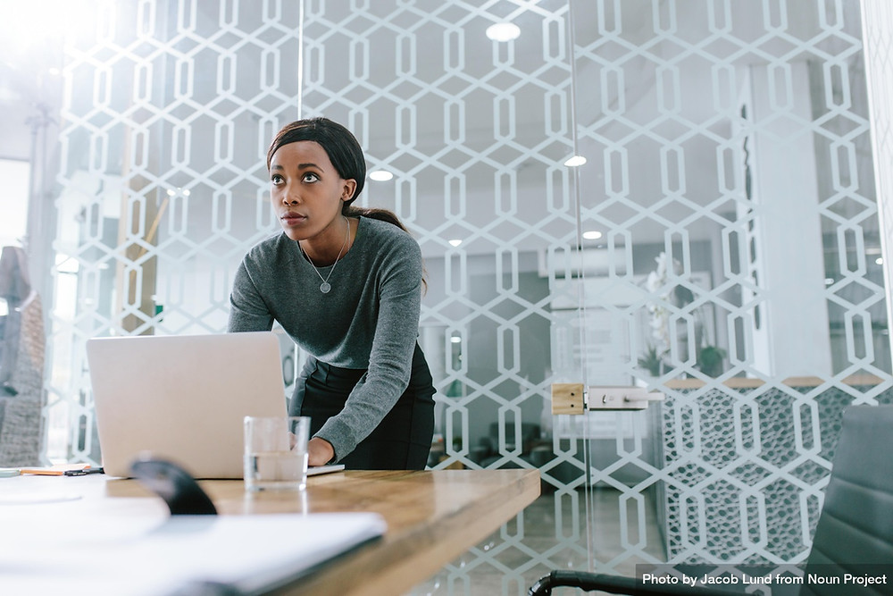 Photo of young African American woman at head of boardroom table. In front of her is an open laptop. She is looking up in the distance ahead of her.