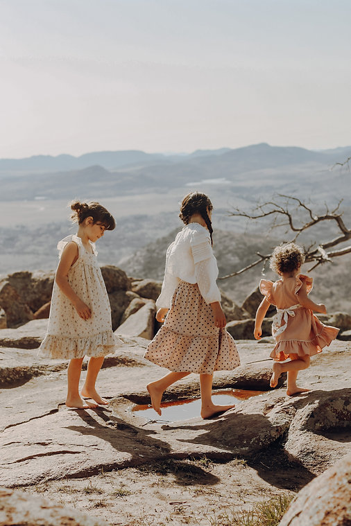 Three young sisters in flowing dresses walking on a mountaintop overlooking a beautiful landscape below.