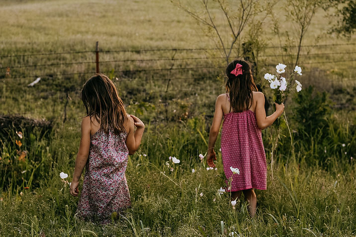 two little girls with long brown hair wearing marron sundresses standing in a field picking wildflowers.
