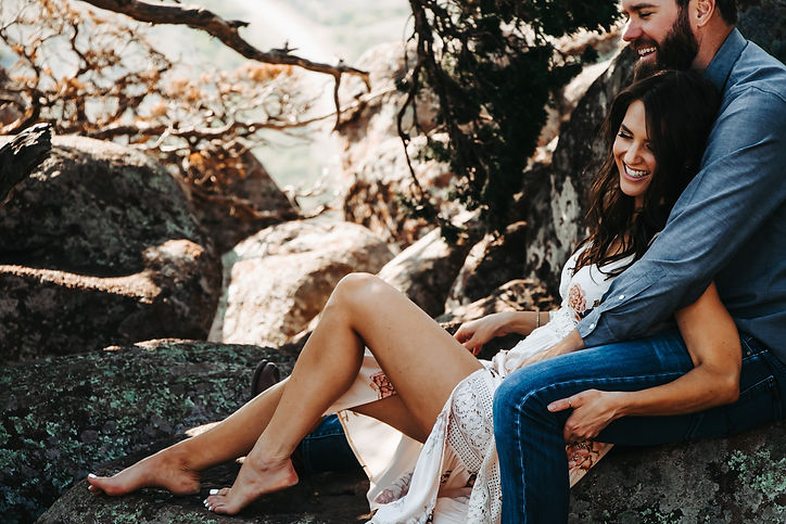 A gorgeous couple sitting on a boulder under a beatiful tree on a mountaintop.  The woman is wearing a sexy white dress and is wrapped in her lovers arms laughing together.