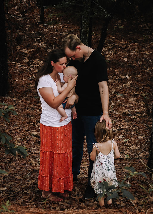 A family of four standing in the wilderness surrounded by pinetrees praying together as the mother who is wearing a white t-shirt a long flowing orange floral skirt holds her shirtless baby boy while kissing his forehead.  The father, in a back shirt and denim pant, has his head gently resting on hers while laying his hand over his young daughter who is standing beside him in a long white sundress.