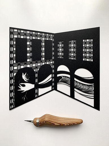 a paper cut art building with an xacto knife