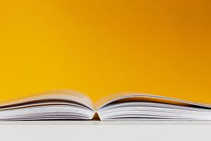 white-book-in-white-table-near-yellow-wa