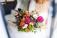 Bride in car with bouquet close-up.jpg