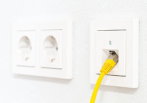 Yellow network cable in wall outlet for