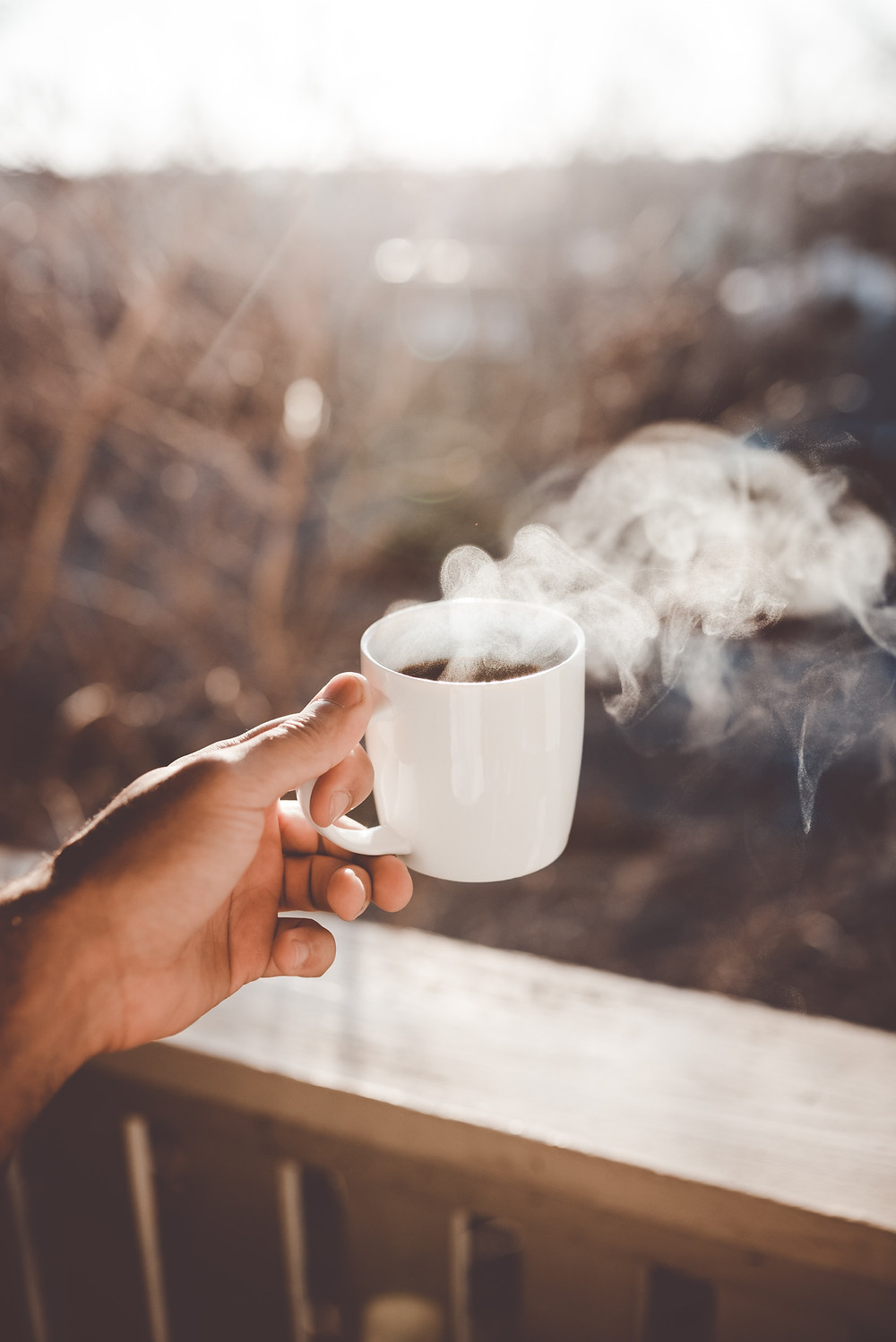 Hand holding a white mug with steaming coffee in it that you can drink before noon to not affect your sleep at night. We help you learn better sleep habits through anxiety counseling in Denver CO and Englewood CO 80209 and 80210