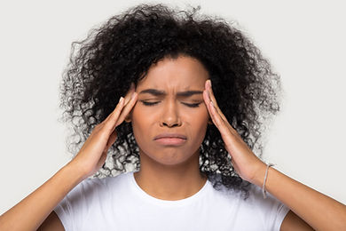 Woman of color looking anxious or having a panic attack with her hands on her head in Englewood, CO before anxiety therapy.  You can get anxiety help in counseling in the Denver area at Catalyss Counseling 80209 and 80210