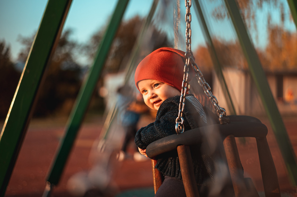 Baby in red hat on a swing at a playground during a playdate with another mom after having a baby in Denver CO. We can help you with your postpartum mood changes and isolation after having a child with our skilled counselors in Englewood CO 80209 and 80210