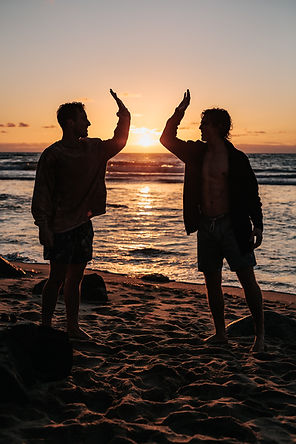 2 men on a beach at sunset connecting and talking with each other after their men's support group.