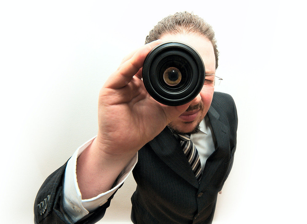 Man in black suit looking through a telescope trying to find a good therapist in Denver CO. Catalyss Counseling has caring and experienced therapists that help you live a balanced life again in Englewood CO 80209 and 80210