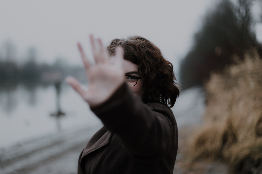 Woman holding up her hand to say no to extra obligations that pulls her away from family or work time in Denver CO. Our caring therapists at Catalyss Counseling can help you balance your work, family, and personal life with stress management treatment in Englewood CO 80209 and 80210