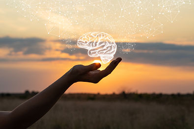 White hand holding an image of a brain against a sunset in Englewood, CO for caregiver stress therapy.  You can get help for caregivers in counseling in the Denver area at Catalyss Counseling 80209 and 80210