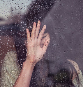 Woman holding hand up to window with raindrops on the outside with head down on hand in distress as a caregiver for her loved one in Denver, CO at Catalyss Counseling 80209 and 80210