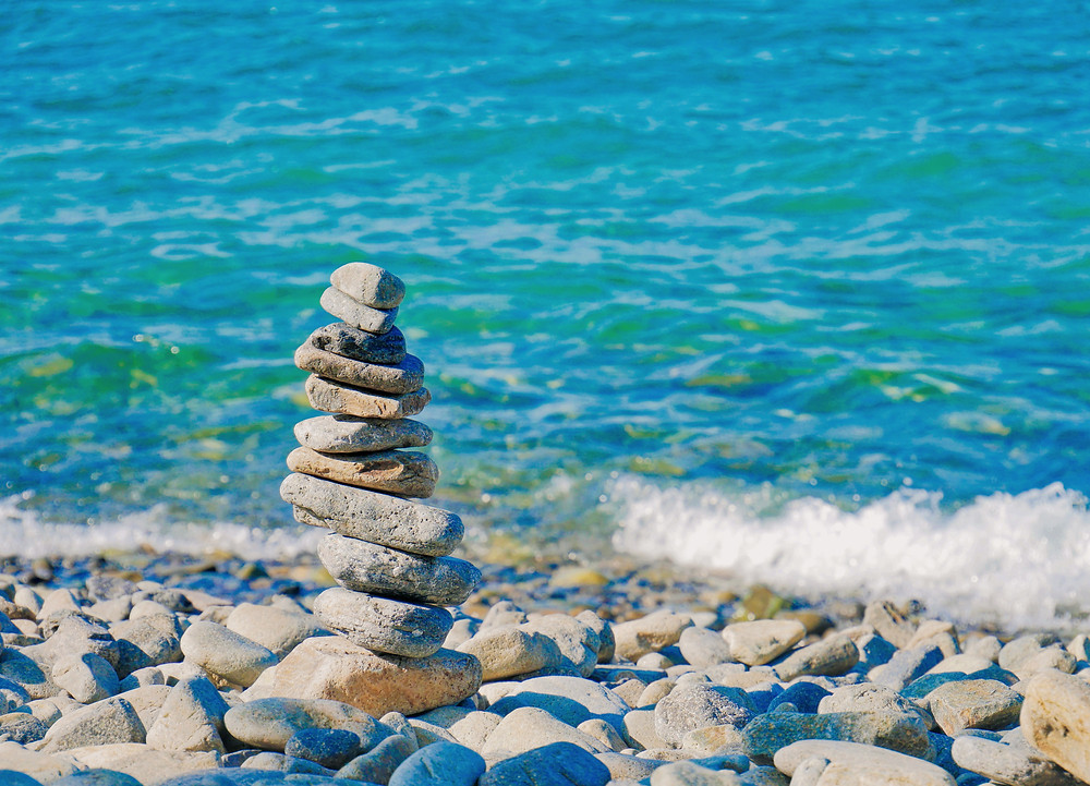 Rocks balancing each other next to the ocean showing us how we can bring balance to our lives by meditation and mindfulness in Denver CO. Our caring therapists at Catalyss Counseling can help treat anxiety with mindfulness in Englewood CO 80209 and 80210