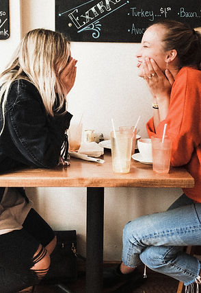 2 women sitting and talking and having coffee together getting mutual support after a women's support group.