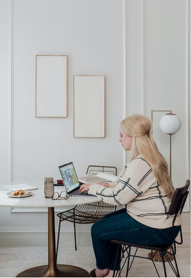 Female sitting at her computer working, at a table at home, doing her marketing consultation group with other private practice owners to grow her business.
